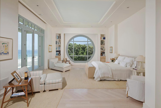master bedroom with ocean view, blue accented circle shaped window and matching glass door, two ottomans in the corner and wicker chairs