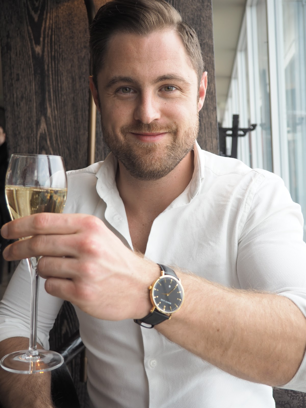 A Man with a glass of champagne wearing a watch at Afternoon Tea at GONG Bar at the Shangri La at The Shard