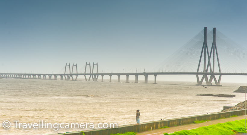 When in Mumbai, we drove around few of the popular places in Mumbai and Travellingcamera visited Sea-link twice in 2 days and loved shooting here. Sea Link connects old Mumbai with new city. This Photo Journey shares more photographs of Sea Link and places from where this beautiful bridge is viewed and clicked.I was staying at JW Marriot near Airport and didn't want to go to other side of Mumbai city  and there is a toll at beginning of Sea Link. So we went till the beginning of Sea Link and took u turn from left after clicking few shots of sea, sea link and high-rise buildings on other side of the sea.I was not happy with what I clicked at this place, so planned to come again but overall all the photographs in my opinion are average. I have seen some of the stunning photographs on web but then realized that I needed to know more about the geography of the place and what makes the best choice to shoot Sea Link.The weather was rainy and it was hazy all around. I clicked some of these plain shots of high-rise buildings on other side of the sea.After taking u turn before the sea link starts, we went to bandstand. After little disappointment about Shahrukh Khan's house at Bandstand, we headed towards Taj LandsEnd and came across these amazing views of Sea link. This certainly is beautiful place to shoot Sea Link and I was imagining how the bridge would look in night when lights on the bridge shine.Next day, plan was to visit Gateway of India and we had to cross the Bridge, so we planned to stop our cab again. Light was a little better, but there was hardly any scope of moving around and trying different things and we were in little hurry.Now we had to cross the bridge, but stopping the cab on bridge was not allowed and our driver strictly conveyed the same to us. So we calmly sat on the back seat and made our cameras to shoot while driving.As we hit the bridge, it started raining heavily and now wiper was also running on the front glass. So we had to manage our clicks in such a way that we shoot front view without much distraction :)Mumbai rains are crazy and very unpredictable. That was one of the main reason that we booked the cab for whole day. It was my first attempt to book Ola cab for whole day and it was not so bad, like my earlier experience with Ola.Overall it was fun driving around Bandra-Worli sea link and clicking these photographs. I wish to spend more time in Mumbai and understand these places in better way.
