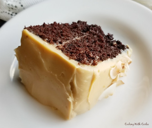 slice of chocolate cake with caramel frosting and toasted coconut flakes
