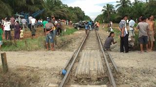 Warga menyaksikan mobil yang ringsek akibat ditabrak kereta api.