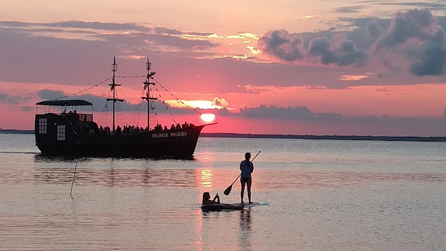 Paddleboarders and the Black Pearl at Sunset