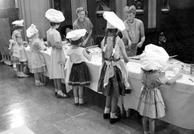 Young ladies dressed in fancy dresses and bakers caps for 1953 baking contest