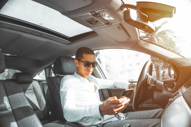 Man with glasses using his smartphone inside a car