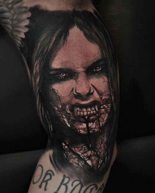 An arm tattoo of an zombie girl with blood dipping from her mouth