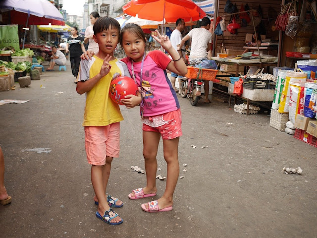 boy and girl with red ball posing for a photo in the middle of Lian'an Street in Zhuhai, China