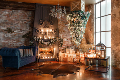 A rustic, lodge-type room with a fire and candles burning and a hanging, upside-down Christmas tree
