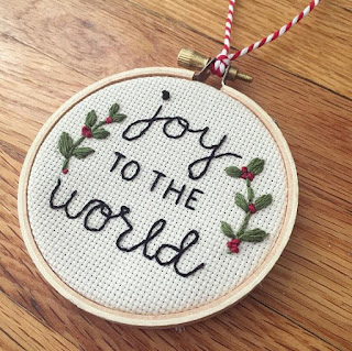 embroidered Christmas ornament from Ollie and Ellis reading Joy to the World with red and green decorative foliage