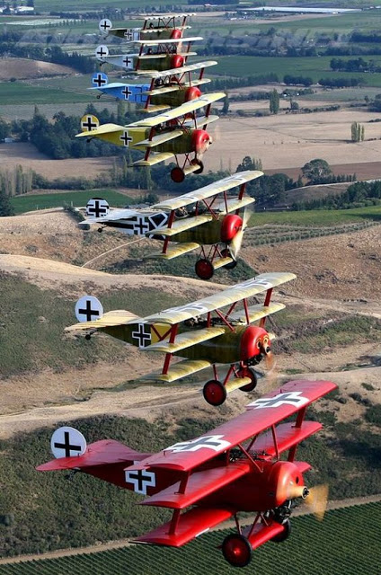 Modern photo of seven refurbished German WWI era TRI-PLANE FIGHTER BRIGADE flying in formation. Dogfights and other stories of pilots. marchmatron.com