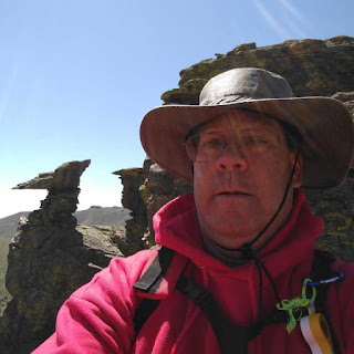 Bondy with pterodactyl shaped hoodoo in background during a hike.