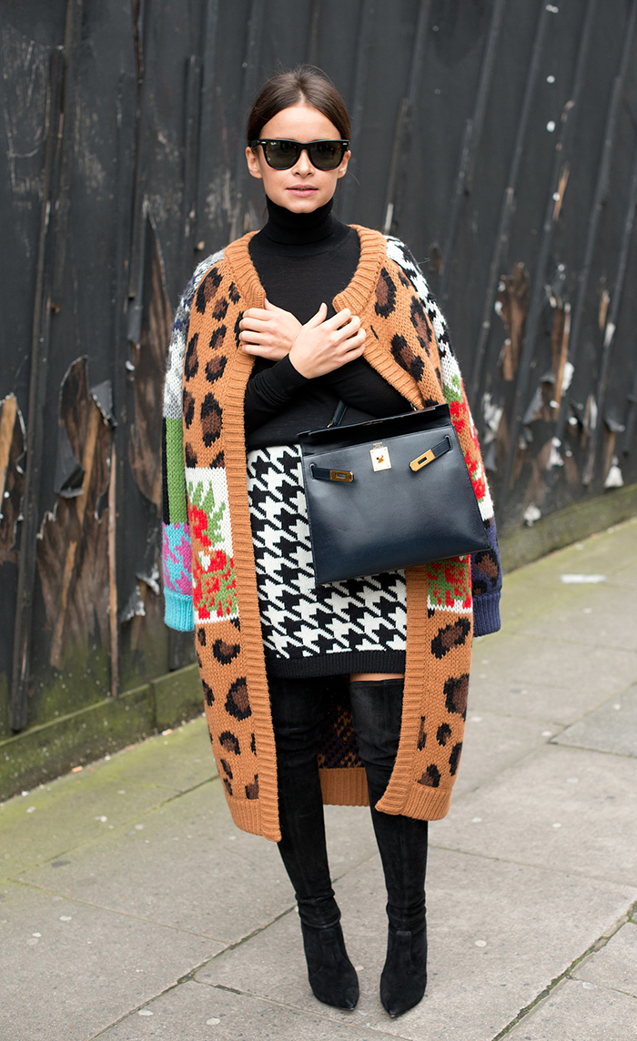Stylista Miroslava Duma wears her printed coat over a houndstooth printed skirt, boots and hermes bag