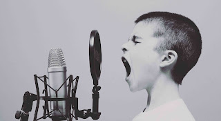 Very young person with microphone depicting the inexperienced voice over artsits doing their own voice over recording.