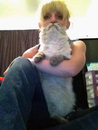 Kucağındaki kedi nedeniyle bıyıklı ve sakallı görünen sarışın bayan