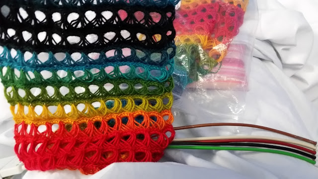 The broomstick crochet scarf is held up on the left hand side. Every row is a different colour. Next to it on the right hand side is the collection of coloured ECG leads.
