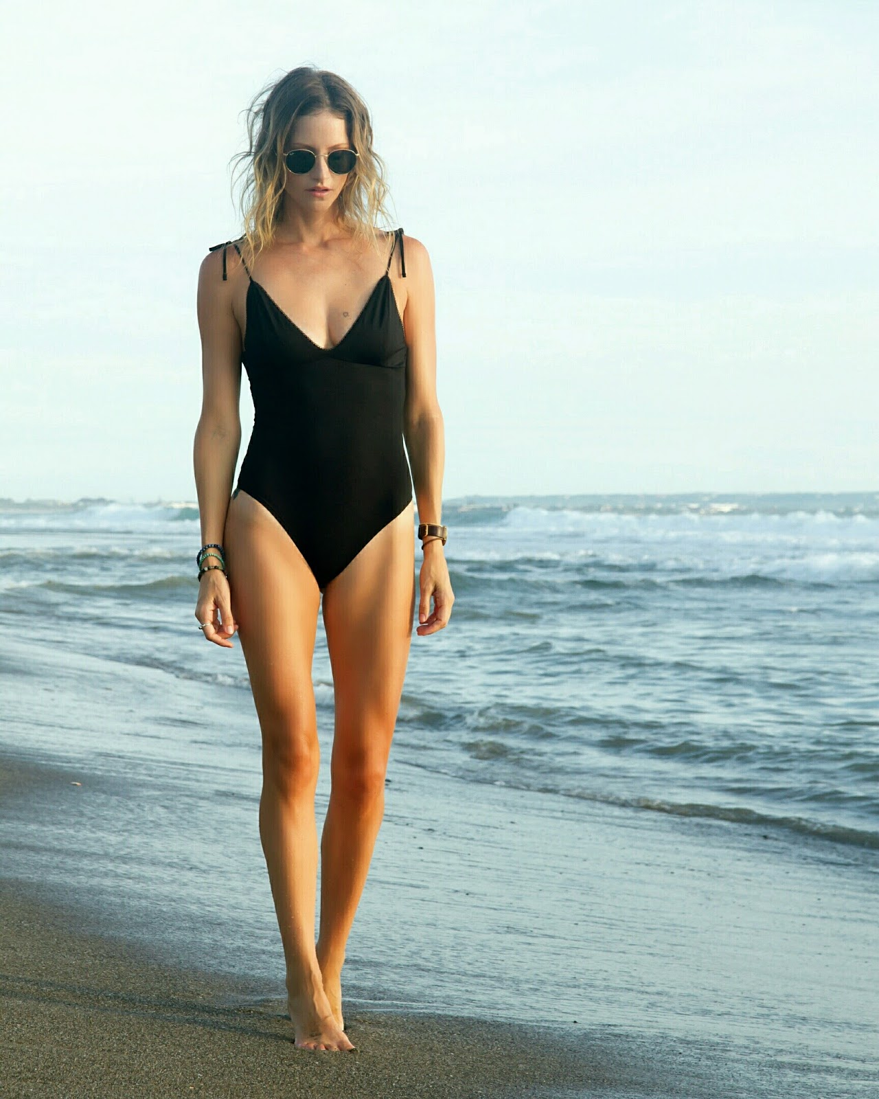 Fashion and travel blogger, Alison Hutchinson, in a black one-piece swimsuit at the beach in Bali