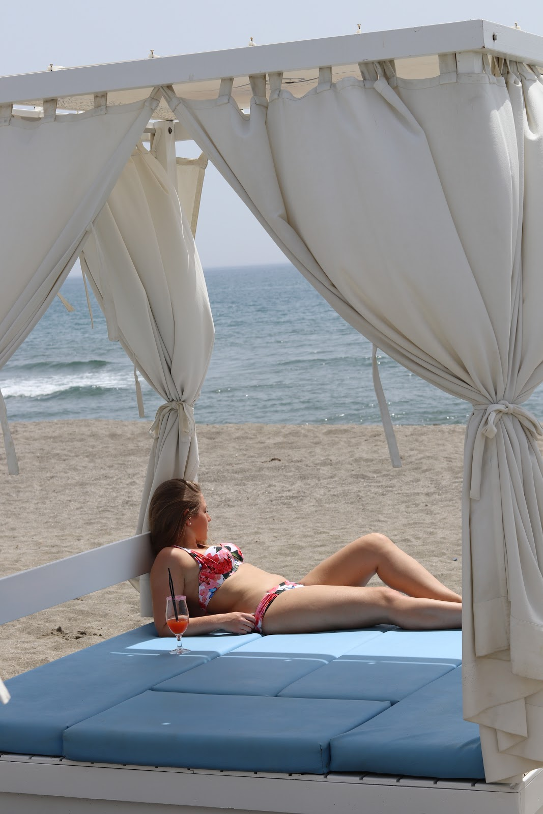 Blonde girl sunbathing with a cocktail on a White Day Bed at Chambao Beach Bar, Sotogrande, Spain