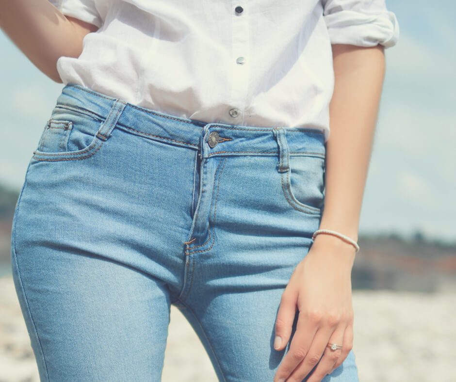 Woman wearing light blue jeans and a white shirt.