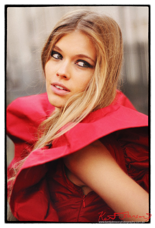 A fashion camapign headshot of Victoria looking back like and angel in a red dress with stiff ruffle butterfly sleeve - fashion photograph on location by Kent Johnson, Sydney, Australia.