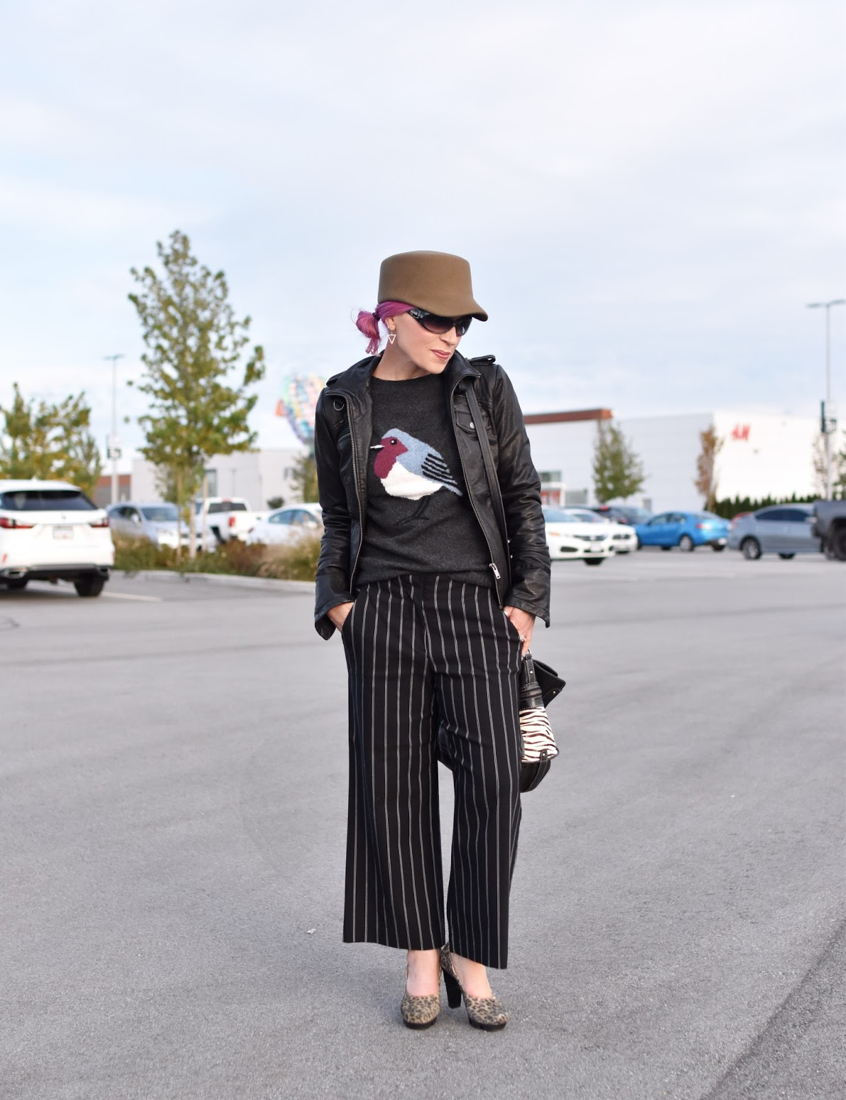 Monika Faulkner outfit inspiration - bird-motif sweater, cropped striped trousers, moto jacket, leopard pumps, military-inspired cap