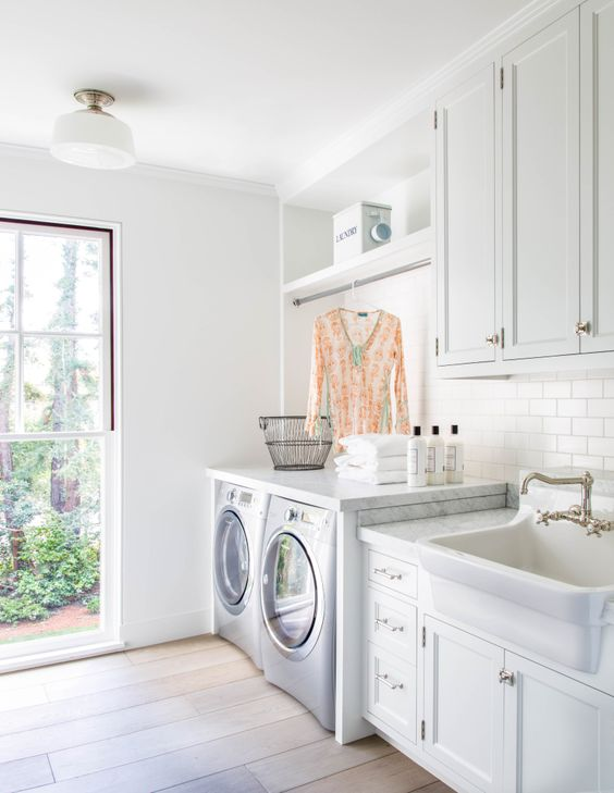 Stunning white laundry room with modern farmhouse style by Giannetti Home