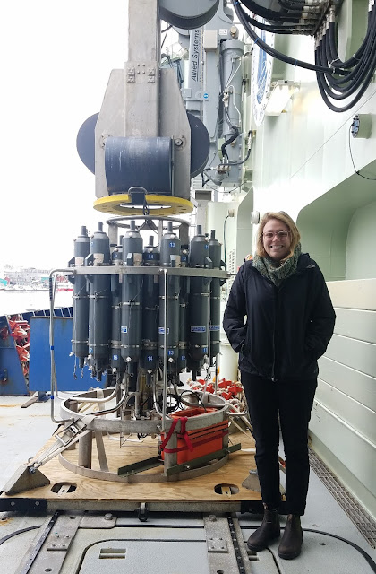 Photo of a smiling young woman standing on the right of the photo, with an equipment set up featuring a rosette and CTD to the left. The equipment stands about 5-6 feet tall, and has 3 metal bands which are about 2 inches wide around a central metal pole. Around the pole, contained within the metal bands, are gray cylindrical flasks arranged vertically and labeled with numbers (the rosette). Below the flasks, there are a series of metal and plastic tubes attached to black sensor boxes (the CTD and other sensors). Also visible is an orange box attached to the lowest metal band. The girl and equipment are on the deck of a vessel, with the ship railing and a small amount of seaside port visible in the background.