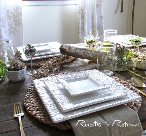 Rustic centerpiece idea using driftwood and succulents with white dishes.