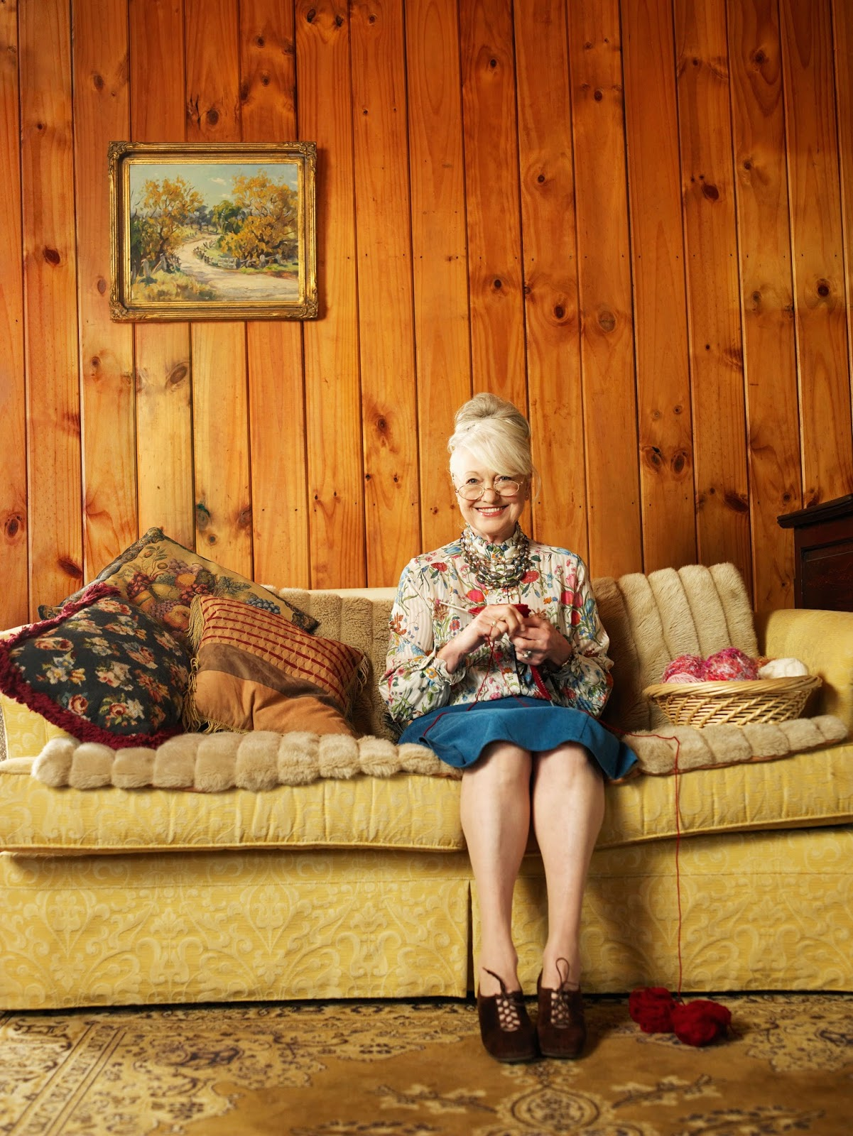 Woman sitting on a bright yellow sofa behind wood panelling