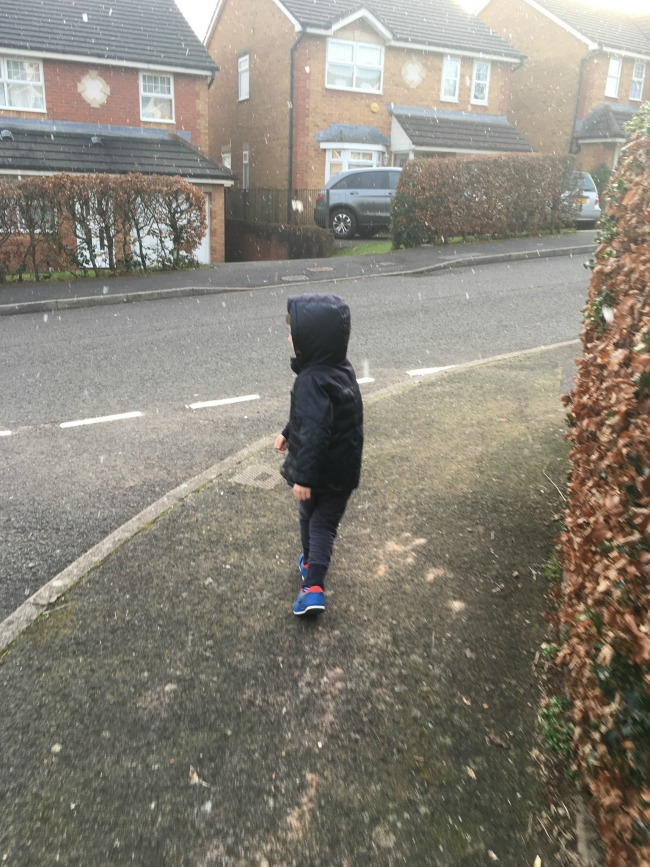boy-stood-in-residential-street-with-very-few-flakes-of-snow.