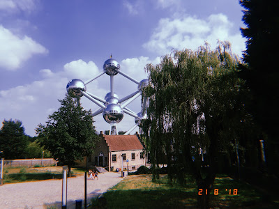 brussels atomium in the sun with green trees in the forefront