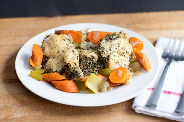 The finished herbed crock pot chicken dinner on a plate with the vegetables.
