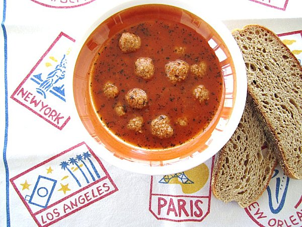 A bowl of Armenian meatball soup with wheat toast on the side