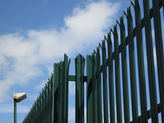 Spiked Metal Security Fence, Lampost and Blue Sky with Clouds
