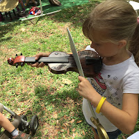 little girl creatively playing a violin with a plastic sword