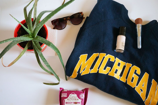 Left to right: Aloe Vera plant, Tortoiseshell sunglasses, Blue Sweatshirt with Michigan in yellow, Livias Kitchen Biccy Boms; Make up brush and Body Shop Foundation