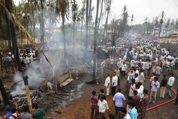 "Indian residents gather at the site of a gas explosion in Nagaram on June 27, 2014. A massive explosion on a state-owned gas pipeline running through the southern Indian state of Andhra Pradesh killed at least 16 people and gutted scores of homes, a state minister said. ""At least 16 people are dead. We have recovered 13 bodies so far,"" state home minister N. Chinna Rajappa told AFP after the blast near a refinery in the East Godavari district."
