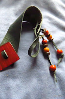 LoveLea's dark green leather bracelet with red vintage button., close up