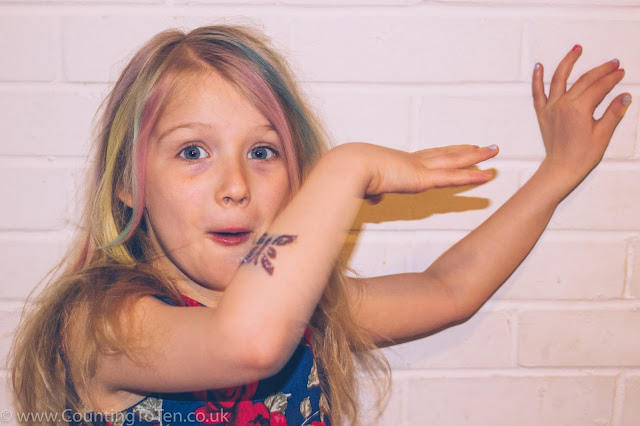 A young girl doing a silly pose to show off her nail polish, glitter tattoo and coloured hair
