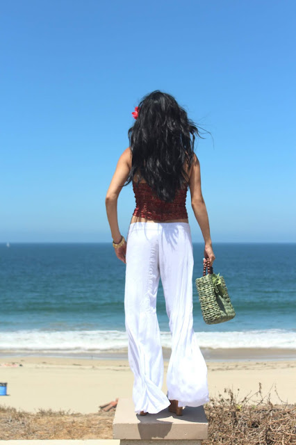 Joanna Joy A Stylish Love Story Blog petite fashion blogger lifestyle blogger beach photo california beaches white flowy pants hibiscus flower green straw purse long black hair Califoria fashion blogger boho chic global chic global fashion