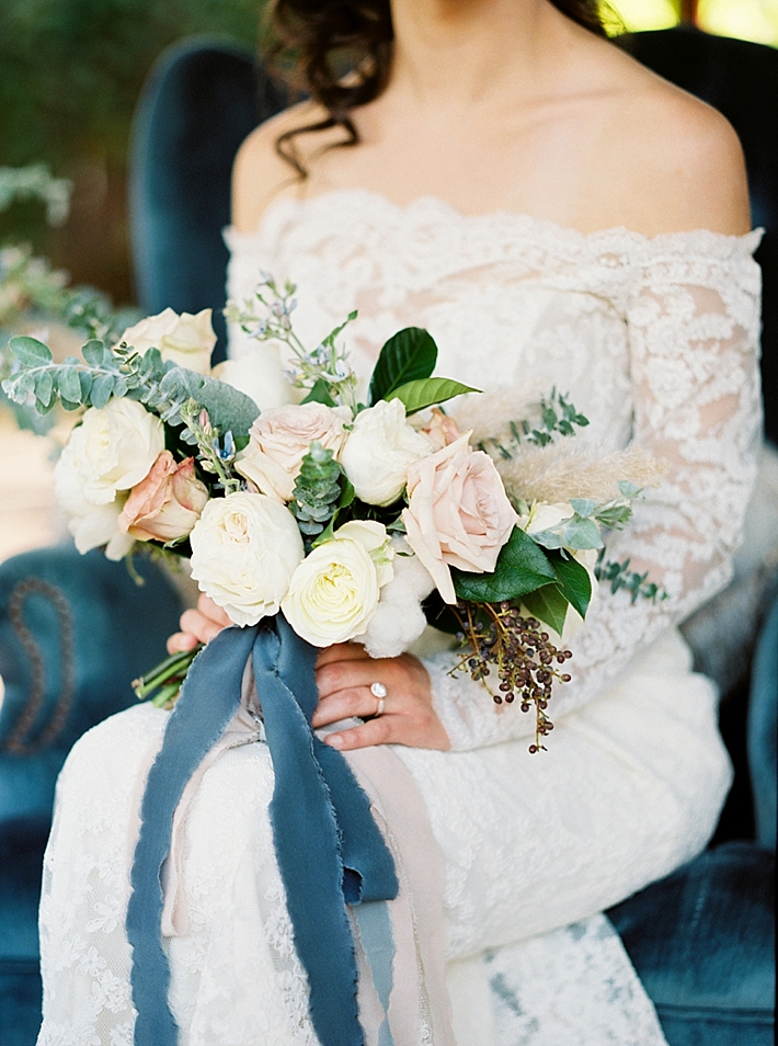 Stunning white and peach bouquet with greenery, berries, and blue ribbon | Photo by Dennis Roy Coronel | See more on thesocalbride.com