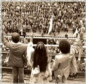 Living Sound, ca. Aug. 15, 1974, sings to a gathering of 300,000 pilgrims at the Festival of the Black Madonna at Jasna Góra Monastery, Częstochowa, Poland. Cardinals Wyszynski and Woytła sat about where the photographer is standing in this photo. Pictured (L/R) are translator Ryszard Pruskowski, Carol Tedder (One Republic Ryan Tedder's aunt), and Tim Hoover. Michael McKibben is playing trombone in the band to the left of this shot
