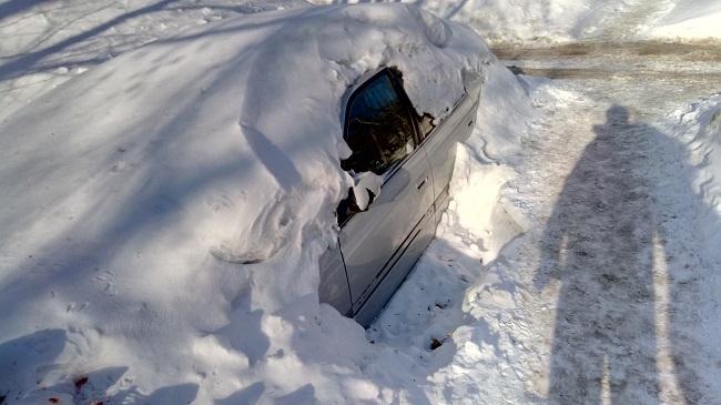 Автомобиль полностью под снегом с откопанной водительской дверью