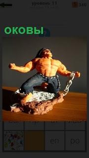 Фигурка мужчины с голым торсом, который рвет оковы, показывая свою силу