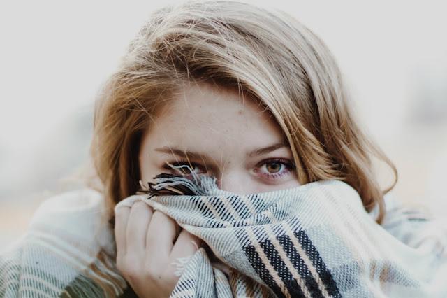 mujer tapa la boca con bufanda para protegerse del resfriado