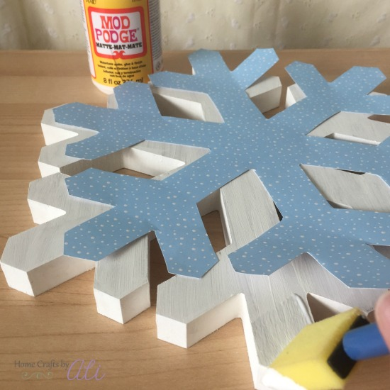 brush mod podge onto wood snowflake and paper