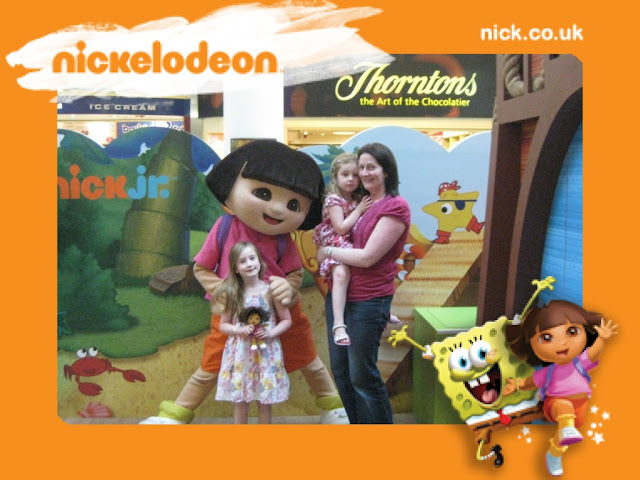 Theme park picture with text Nickelodeon and mum Steph standing holding Sasha, with a lifesize Dora holding shoulders of Tamsin