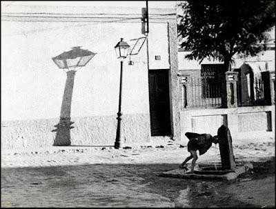 Foto antigua en la que se ve un niño agachado bebiendo de una fuente pública