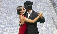 Kırmızı elbiseli bir bayanla taş döşeli bir yolda dans eden takım elbiseli ve şapkalı bir adam