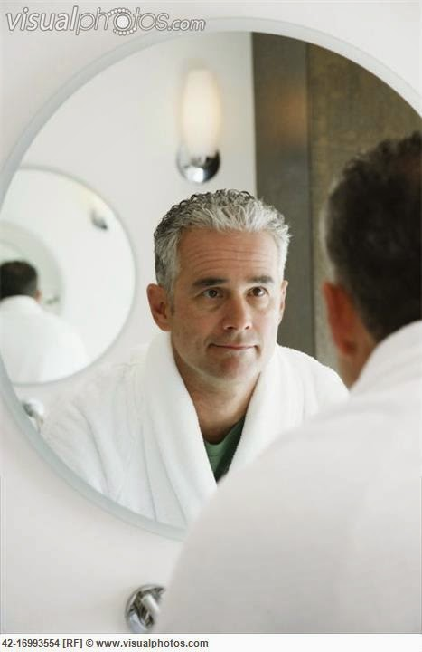 older man looking in mirror