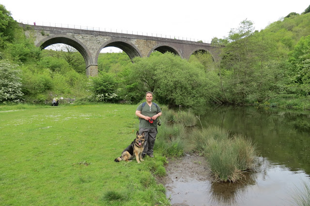 Rich and Lotte stand on the river bank with the arches of the Victorian viaduct behind them.