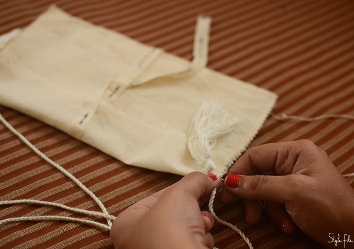 An image of tassels being sewn onto cream cloth by a woman with orange nails for a do-it-yourself mini crossbody sling bag project on Style File